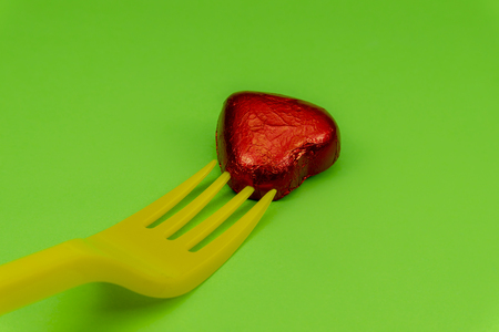 Heart-shaped chocolate candy in red foil and yellow disposable plastic fork, viewed in close-up on green background. The concept of breaking hearts by womanizer or seducer and betrayal Stockfoto