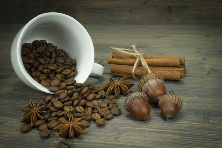 Roasted coffee beans spilling from a cup, acorns and cinnamon with star anise spice on a rustic wooden table in a close up view
