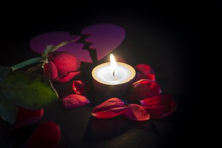 Vela de té y corazón roto, pétalos de rosas rojas con poca profundidad de foco con una reflexión sobre fondo negro