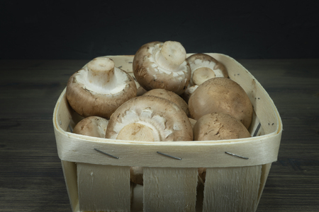 Fresh whole crimini (Baby Bella) mushrooms in the wooden basket on dark rustic table background