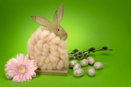 Colorful green Easter still life or card design with cute little woolly rabbit decoration, fresh spring flower and foil wrapped Easter eggs with copy space for your holiday message
