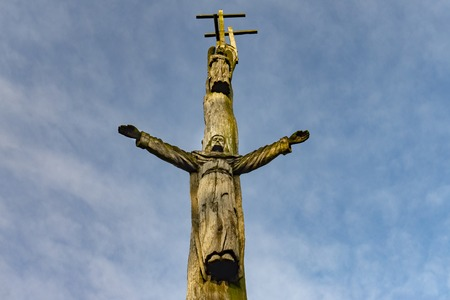 Rustic hand carved figure of Christ with outspread arms on a tree looking up from below against a cloudy blue sky