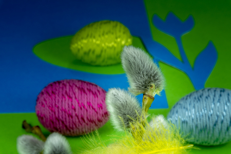 Willow buds, Easter eggs and feather in close-up as a set of decoration on spring theme in Christianity, placed on green background with flower cutout of blue paper