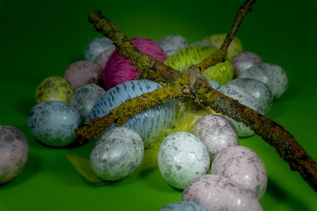 Handmade Easter eggs, feather and cross of twigs in close-up on green background. Christian symbols of Palm Sunday or Easter