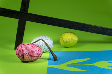 Handmade Easter eggs, antique nail, cross and blue paper cutouts in close-up on green background. Christian symbols of Palm Sunday or Easter Stockfoto