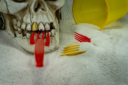 Pirate skull toy with red plastic fork in teeth, straws, disposable glass and sand, viewed from high angle in close-up. Funny Jolly Roger, plastic waste problem concept