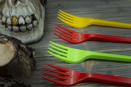 Pirate skull toy and colorful plastic forks on wooden background in close-up. Plastic waste problem concept