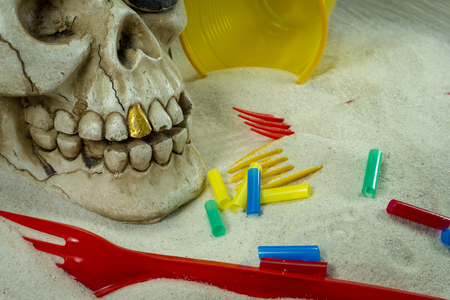 Pirate skull toy with plastic forks, straws, disposable glass and sand, viewed from high angle in close-up. Funny Jolly Roger, plastic waste problem concept