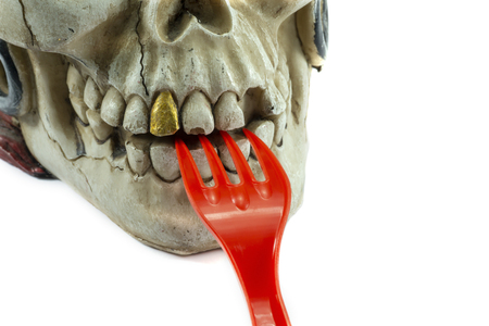 Pirate skull toy with red plastic fork in teeth, viewed in close-up against white background. Plastic waste problem concept Imagens