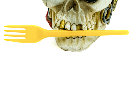Pirate skull toy with yellow plastic fork in teeth, viewed in close-up against white background. Plastic waste problem concept Stock Photo