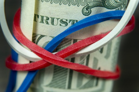 Roll of USD bills with red, white and blue rubber band in a close up view, conceptual of trade, business, investment, savings, retirement, finance and money
