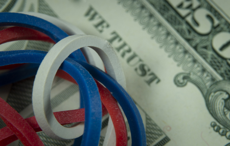 Twisted red, white and blue rubber bands on dollar banknote in a close up view, conceptual of trade, business, investment, savings, retirement, finance and money Imagens