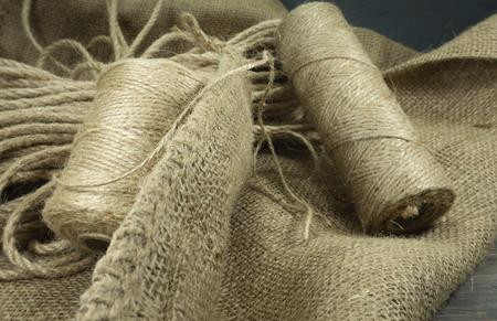 Zwei Spulen Jutefäden oder Juteschnur und Leinenseilspule auf Sackleinenstoff in Nahaufnahme auf grauem Hintergrund Standard-Bild