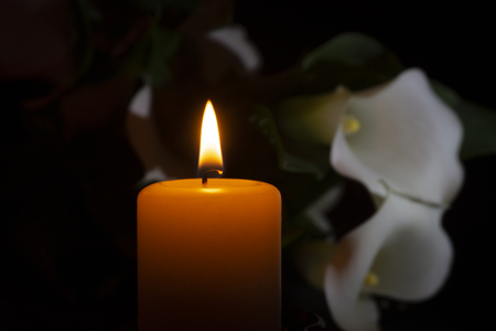 A close up of an orange candle and flame and lily flowers on a dark background. Stock Photo