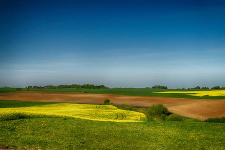 Paisaje agrícola con colinas, campo agrícola arado, prado y árboles en un campo