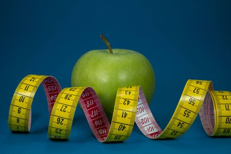 Weight loss and healthy diet concept with measuring tape and green apple on blue background