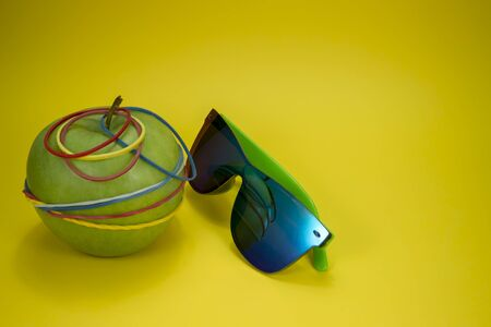Green apple tied in colorful rubber bands and fashion sunglasses over a yellow background. Simplicity back to school or diet, aerobic concept with copy space Stock Photo