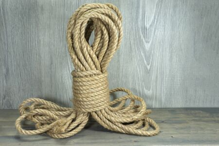 Twisted burlap jute twine rope in close-up on grey rustic background