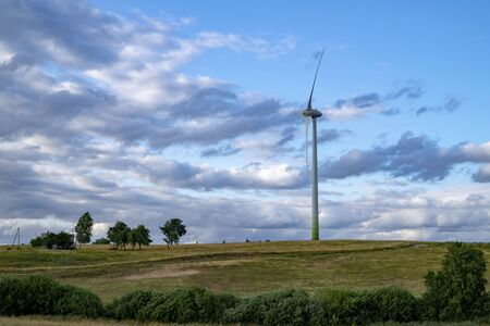 Wind power turbines for electric power generation in landscape with green grass, trees and cloudy blue sky