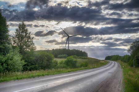 Wind power turbines in landscape with road, green grass and cloudy blue sky Stock Photo
