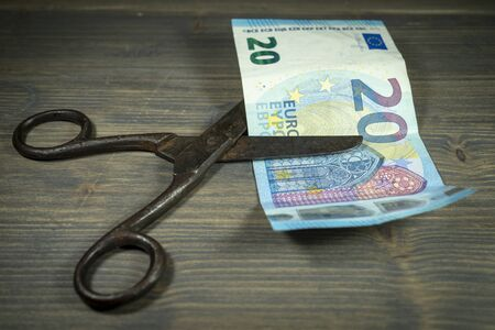 Old vintage scissors cut twenty EUR banknote over rustic wooden background. European Central Bank interest rate cuts concept Imagens
