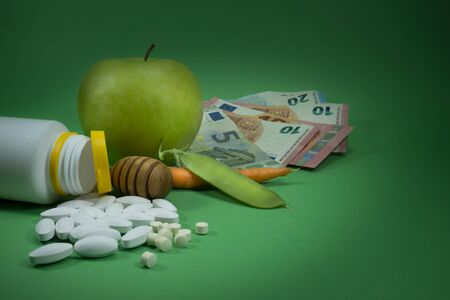Pills spilling out of a white bottle near apple, pea pod, carrot and euro banknotes on a green background. Healthcare, diet or weight loss concept