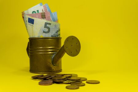 Euro banknotes of assorted denominations in a copper watering can with scattered coins on yellow with copy space for financial themes
