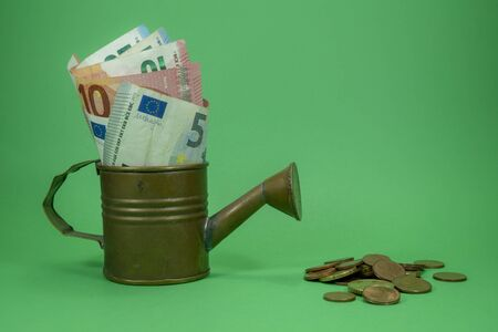 Euro banknotes of assorted denominations in a copper watering can with scattered coins on green with copy space for financial themes