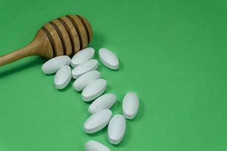 Wooden honey wand with scattered pharmaceutical pills on a colorful green background with copy space in a healthcare concept