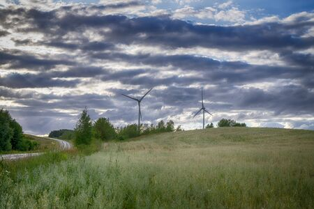 Road and wind power turbines for electric power generation over hills and gloomy rain clouds surrounding