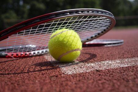Cohete de tenis de primer plano sobre pelotas en la superficie de canchas duras vista de ángulo bajo Foto de archivo