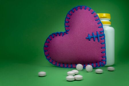 Medical pills and medical bottle near hand stitched fabric heart on a green background. Drug therapy and blood pressure concept 스톡 콘텐츠