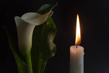 Eine Nahaufnahme einer orangefarbenen Kerze und Flamme und Lilienblumen auf dunklem Hintergrund. Standard-Bild