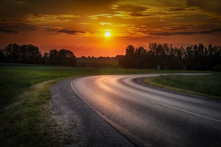 Vivid orange tropical sunset over woodland trees with a curving tarred road reflecting the color in the foreground in a scenic rural landscape