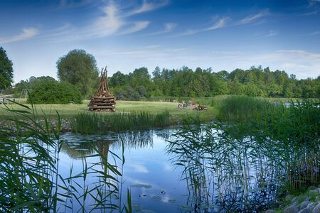 Tranquil lake with large ready built bonfire on the further shore waiting to be lit in the evening for a celebration or party Banco de Imagens