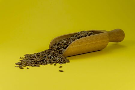 Flax seeds spilling from a wooden scoop, copy space on yellow background Stockfoto