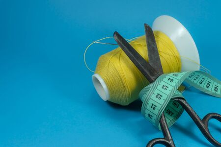 Old metal scissors wrapped around with tape measure and spools of thread on blue background, needlework and tailoring concept with free copy space