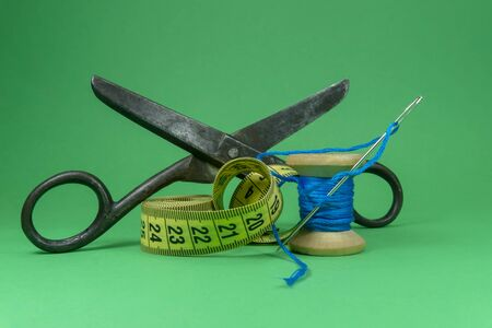 A close up image of a tape measure, old metal scissors, spool of blue thread and sewing needle on green background, handmade sewing, needlework and tailoring concept Stock Photo