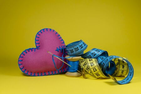 Hand stitched fabric heart, tape measure and spool of thread with needle on yellow background, handmade sewing, needlework and tailoring concept