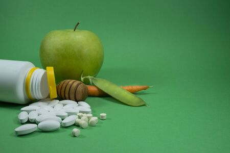 Pills spilling out of a white bottle near apple, pea pod and carrot on a green background. Healthcare, diet or weight loss concept