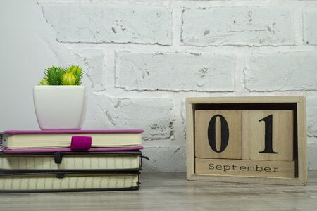 September still life with books, potted plant and rustic sign for the month against a white brick wall