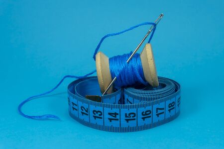 A close up image of a tape measure, spool of blue thread and sewing needle on blue background, handmade sewing, needlework and tailoring concept
