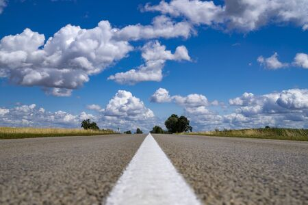 Low angle view of a tarred road receding into the distance in open countryside under a cloudy blue sky with focus to the center white line