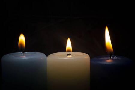 Gros plan de trois bougies de cire colorées flamme sur fond sombre avec espace de copie