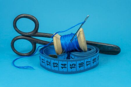 A close up image of a tape measure, old metal scissors, spool of blue thread and sewing needle on blue background, handmade sewing, needlework and tailoring concept