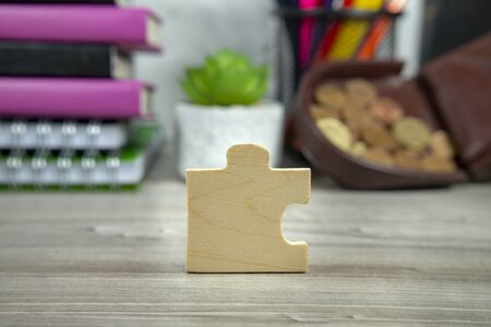 Wooden puzzle piece standing on end on a table with blurred background of books and open purse Stock Photo