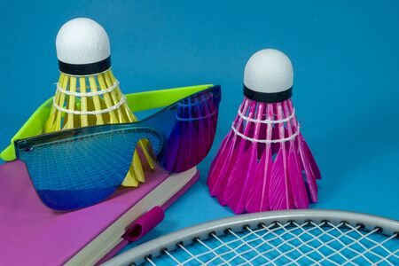 Colorful badminton shuttlecocks with racket and sunglasses resting on a brightly colored pink book or diary over a blue background in a close up still life
