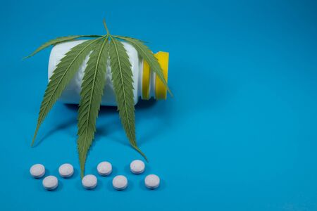 Conceptual medical marijuana image with a cannabis leaf, scattered pills and pharmacy bottle over blue 스톡 콘텐츠