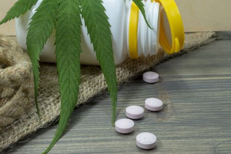 Conceptual types of cannabis products concept image with a cannabis leaf, scattered pills and pharmacy bottle