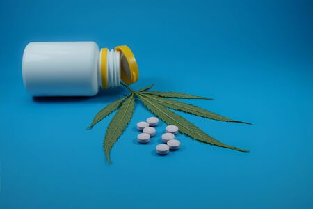 Conceptual medical marijuana image with a cannabis leaf, scattered pills and pharmacy bottle over blue Stock Photo